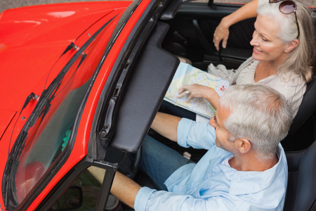 Smiling mature man having a ride with his wife in red convertible photo