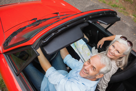 High angle view of cheerful mature man having a ride with his wife in red convertible photo