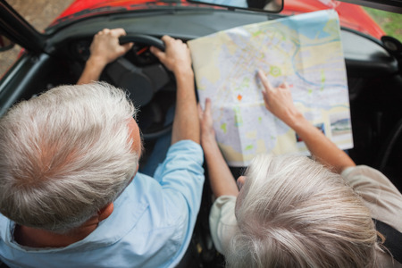 Overhead view of mature couple on holidays reading map in their classy convertible  photo