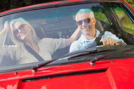 Happy mature couple in red cabriolet going for a ride on sunny day photo