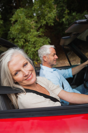 Side view of happy mature couple driving red cabriolet on sunny day photo