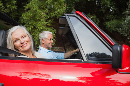 escapism: Side view of mature couple driving red convertible on bright day Stock Photo