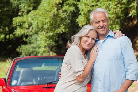 Cheerful mature couple posing against their red cabriolet photo