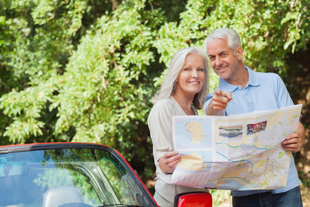 Smiling mature couple by their cabriolet looking for direction photo