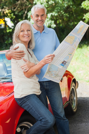 Happy mature couple reading map together by their cabriolet photo