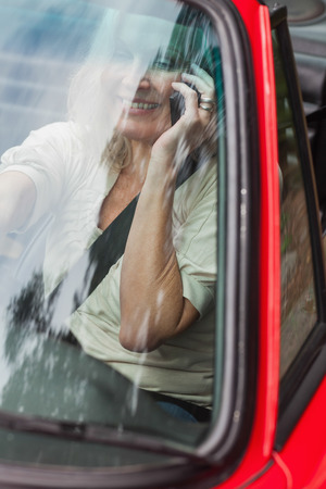 Smiling mature woman on the phone driving red cabriolet on sunny day photo