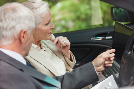 wealthy lifestyle: Business people working together in classy cabriolet on a bright day