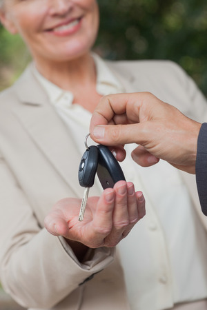Close up on smiling businesswoman being given keys by her partner photo