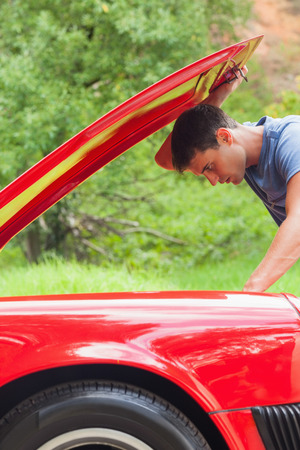 breaking down: Handsome man checking his car engine after breaking down Stock Photo