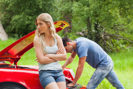 Worried couple waiting for assistance after breaking down with their car Stock Photo