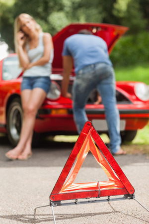 broken car: Close up on triangle warning sign with broken down car on background Stock Photo