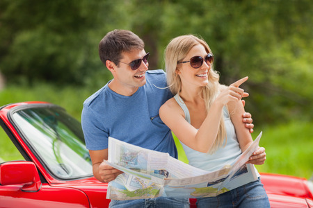 Cheerful young couple on a sunny day reading map  photo
