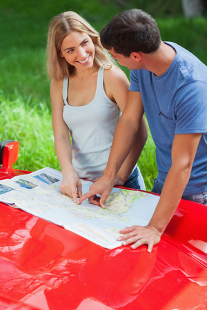 Smiling young couple reading map on their cabriolet bonnet on a sunny day photo