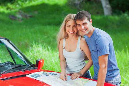 Happy young couple reading map on their cabriolet bonnet on a sunny day photo