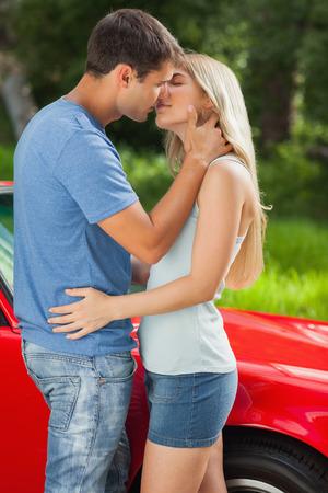 beso: Amantes de la pareja bes�ndose apasionadamente por su cabriolet