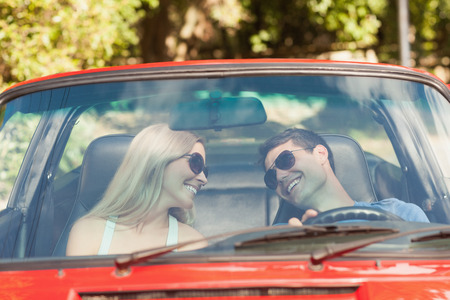 Loving couple in their red cabriolet having a ride on sunny day photo