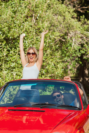 Loving couple having fun in their red convertible on a sunny day photo