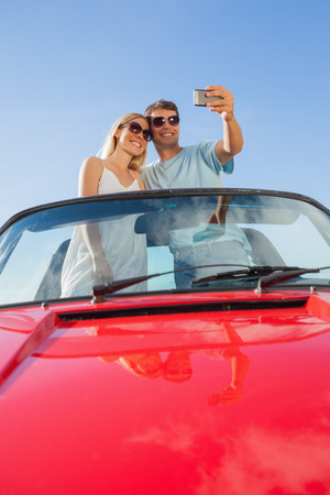 Smiling couple standing in red cabriolet taking picture on a sunny day photo