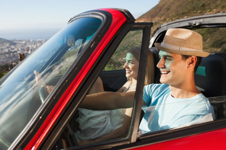 escapism: Smiling couple on their way to the beach in classy cabriolet