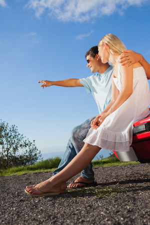 Cheerful cute couple sitting on their cabriolet car hood to admire the panorama photo
