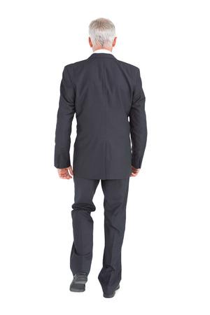 walking away: Businessman walking away from camera on white background Stock Photo