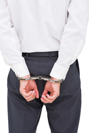 restraining device: Close up on young businessman wearing handcuffs on white background