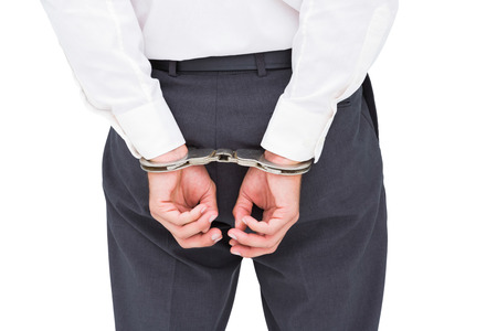 Close up on classy businessman wearing handcuffs on white background photo