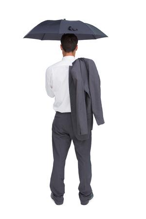 Businessman standing back to camera holding umbrella and jacket on shoulder against white background photo