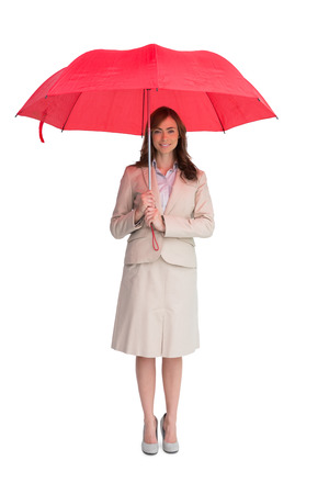 Attractive businesswoman holding red umbrella against white background photo