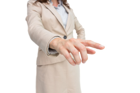 extending: Stylish businesswoman touching invisible screen on white background