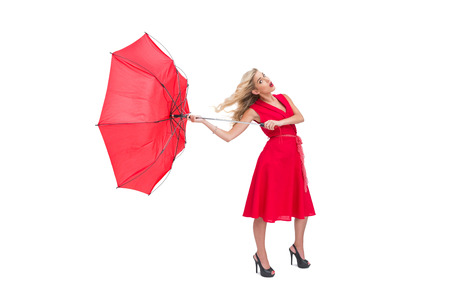 Attractive glamour woman holding a broken umbrella on white background photo