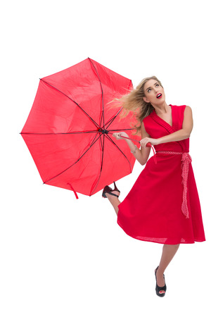 Beautiful woman wearing red dress holding umbrella against white background photo