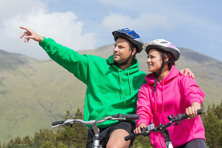 Smiling couple on a bike ride wearing hooded jumpers with man pointing in the countryside photo
