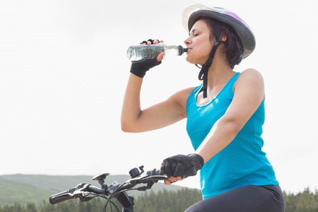 adventuring: Athletic woman on mountain bike drinking water in the countryside Stock Photo