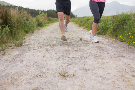 Couples feet running on a trail in the countryside photo