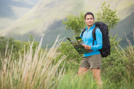 adventuring: Attractive female hiker with backpack holding a map in the countryside