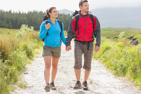 Hikers with backpacks holding hands and walking on a country trail photo