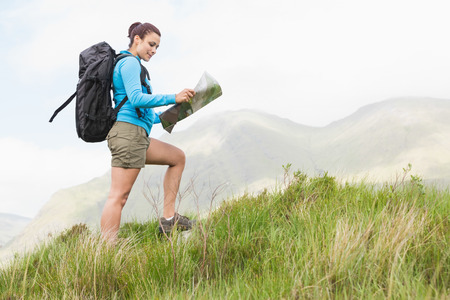 Attractive hiker with backpack walking uphill reading a map in the countryside photo