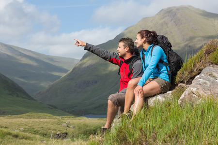 woman hiking: Couple taking a break after hiking uphill with man pointing in the countryside Stock Photo