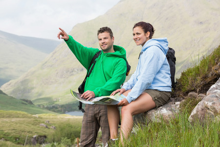Couple resting after hiking uphill and consulting map in the countryside photo