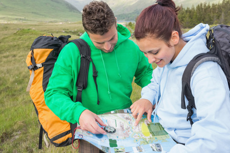 Couple sitting after hiking uphill and consulting map in the countryside photo