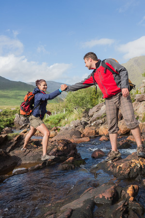 Man helping his pretty girlfriend to cross a river on a hike in the country photo