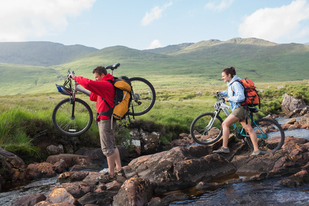 Couple crossing a stream holding their bikes in the mountains