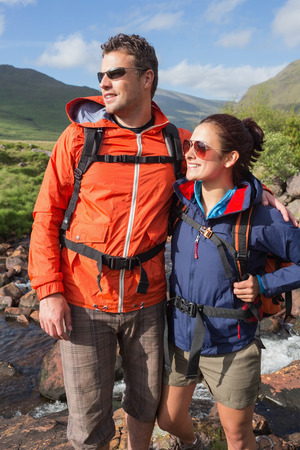adventuring: Couple wearing rain jackets and sunglasses admiring the view in the countryside