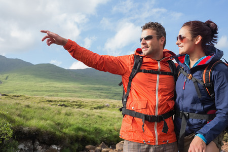 Couple wearing rain jackets and sunglasses admiring the scenery with man pointing in the countryside photo