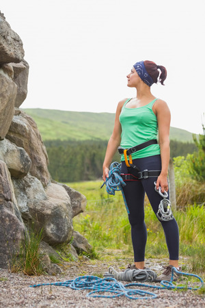 adventuring: Attractive rock climber looking up at her challenge in the countryside