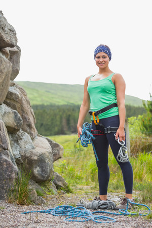 Attractive rock climber smiling at camera in the countryside photo