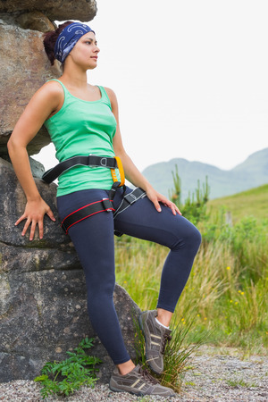 Attractive female rock climber leaning on rock face in the countryside photo