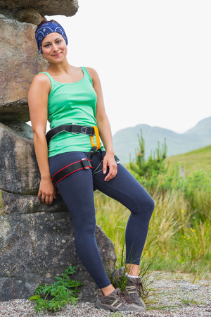 Attractive female rock climber leaning on rock face smiling at camera in countryside photo