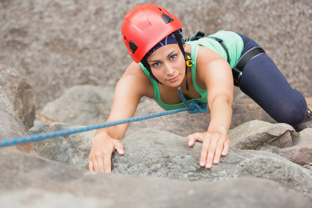 Determined girl climbing rock face looking at camera photo